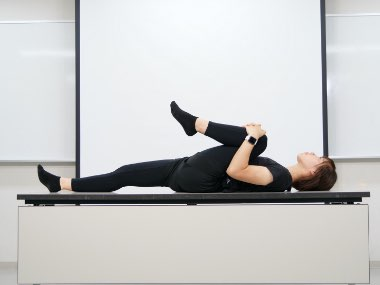 仰臥位で自分の足を抱えて可動域測定
