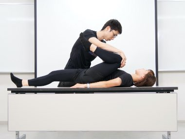 仰臥位で施術家が患者の足を動かして可動域測定